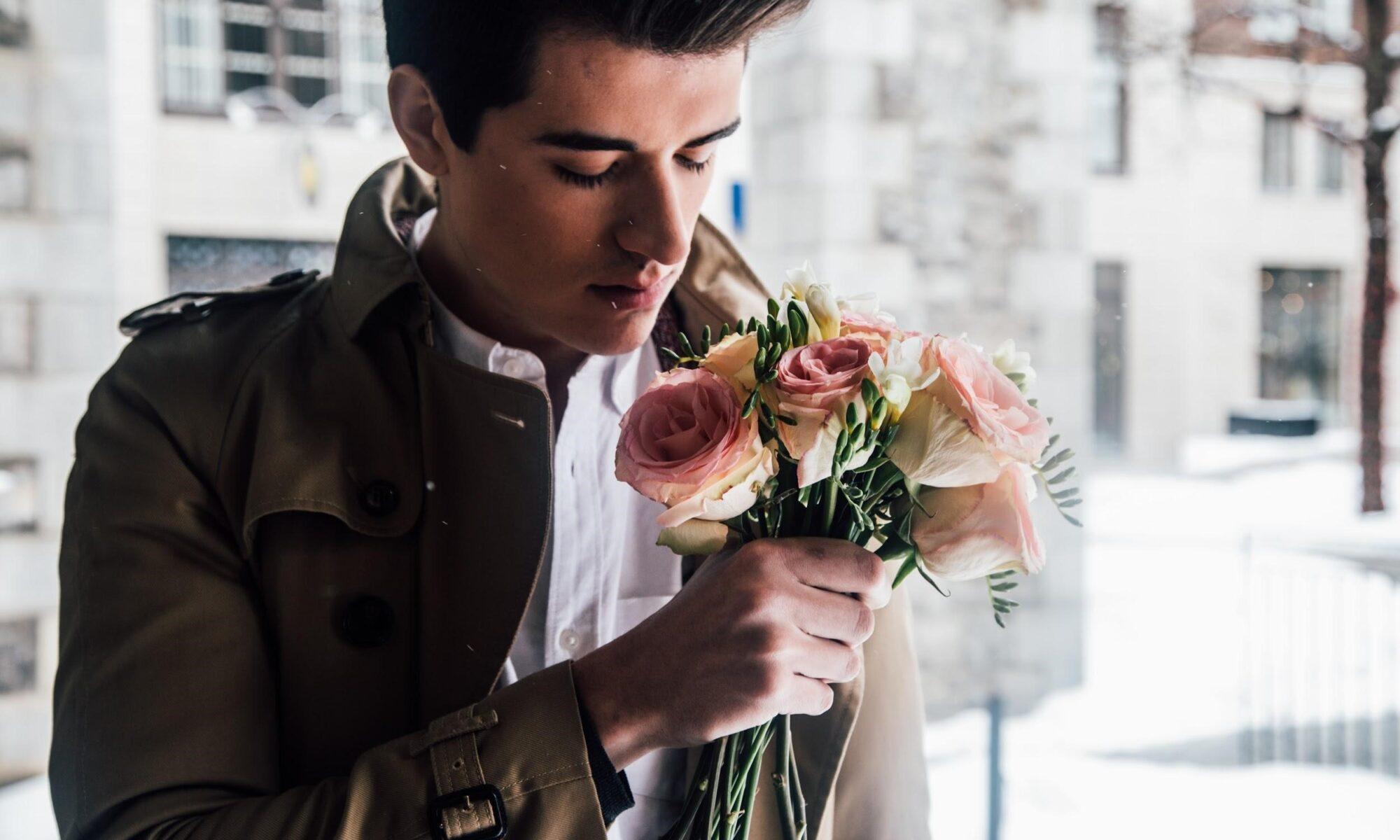 Junger Mann wartet mit Blumen auf sein erstes date